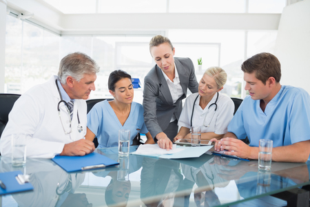 suit: Team of doctors and businesswoman having a meeting in medical office