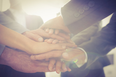 mujeres trabajando: Equipo de negocios de pie manos juntas en la oficina