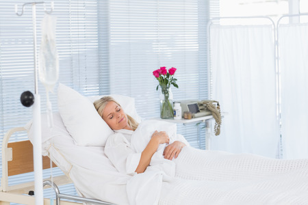 Happy patient lying on her bed in hospital Stock Photo