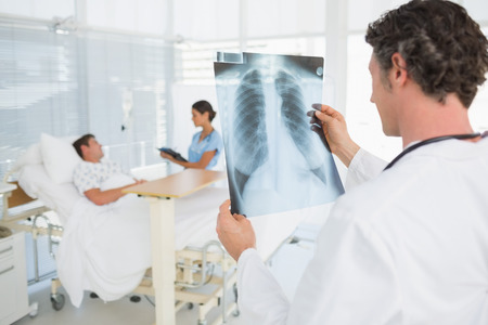 keep watch over: Doctor checking patients xray in hospital room
