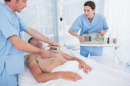 reanimować: Zespół medyczny reanimacji człowieka z defibrylatora w szpitalu Zdjęcie Seryjne