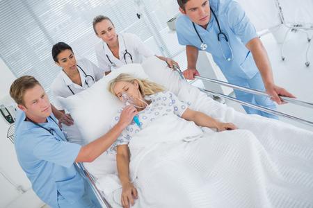 paciente en camilla: Equipo de médicos que llevan al paciente sobre la camilla en el hospital