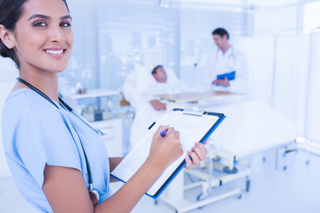 keep watch over: Smiling doctor checking patients file in hospital room Stock Photo