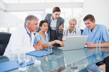healthcare: Team of doctors and businesswoman having a meeting in medical office