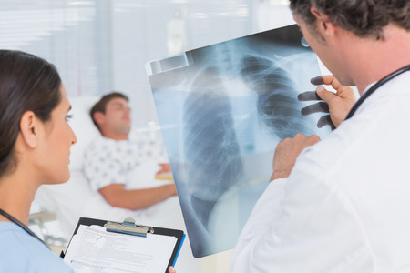 doctor examining woman: Doctors checking patients xray in hospital room