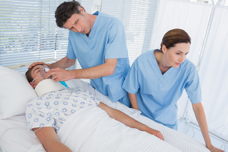 keep watch over: Doctors holding patients oxygen mask in hospital room Stock Photo