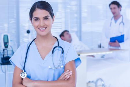 enfermera con paciente: Doctor sonriente mirando a la cámara en la sala de pacientes Foto de archivo