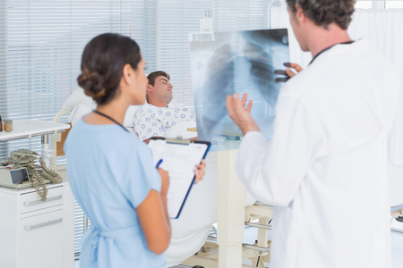 keep watch over: Doctors checking patients xray in hospital room