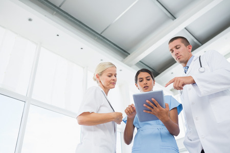 medical doctors: Doctors looking together at tablet in medical office Stock Photo