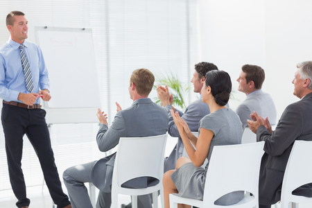 Smiling business team applauding during conference in meeting room Stock Photo