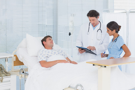 attend: Doctors taking care of patient in hospital room