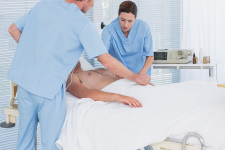 Medical team resuscitating a man with a defibrillator in hospital room Stock Photo