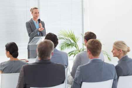 conference meeting: Pretty businesswoman talking in microphone during conference in meeting room