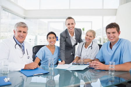 office uniform: Team of doctors and businesswoman having a meeting in medical office
