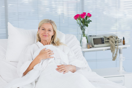 fourties: Smiling patient looking at camera on her bed in hospital Stock Photo
