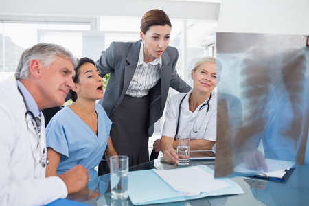 medical doctors: Team of doctors and businesswoman examining xray in medical office