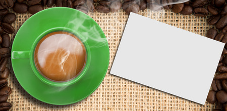 indent: Green cup of coffee against white card