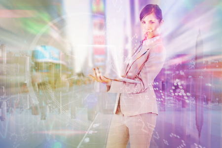 mirror image: Confident young businesswoman with laptop against mirror image of city skyline Stock Photo
