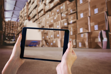 stacker: Finger pointing to tablet against worker with fork pallet truck stacker in warehouse