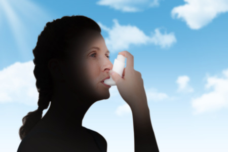 inhaler: Woman using inhaler for asthma against blue sky