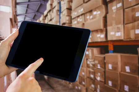 Man using tablet pc against forklift in large warehouse