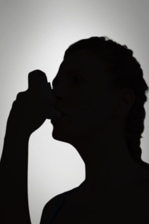 tied hair: Woman using inhaler for asthma against grey vignette