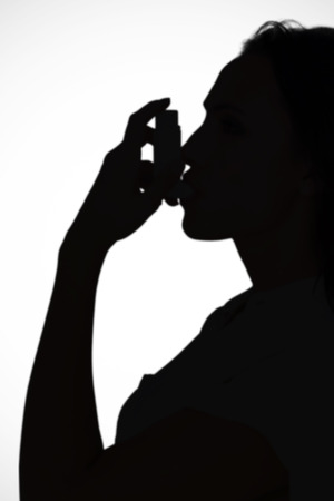 affliction: Asthmatic brunette using her inhaler  against white background with vignette