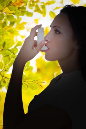 asthmatic: Asthmatic brunette using her inhaler  against detail shot of leaves