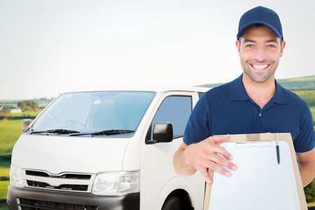 scenic landscape: Happy delivery man with package and clipboard against scenic landscape