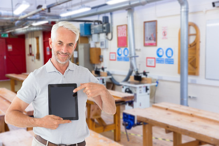 mature student: Mature student showing tablet pc against workshop