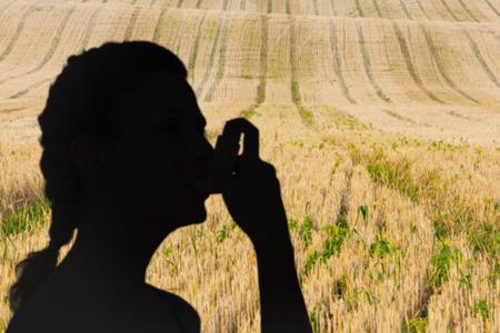 inhaler: Woman using inhaler for asthma against rural fields