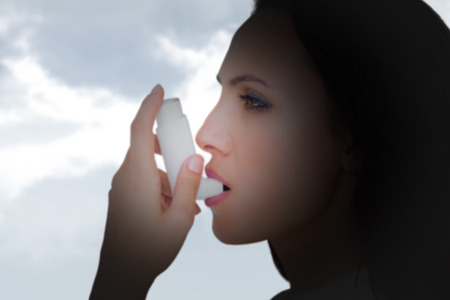 asthmatic: Asthmatic brunette using her inhaler  against grey cloudy sky