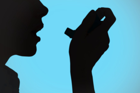 health fair: Close up of a woman using an asthma inhaler against blue background with vignette