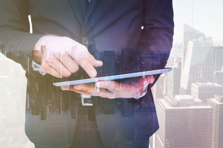 mirror image: Mid section of a businessman touching digital tablet against mirror image of city skyline