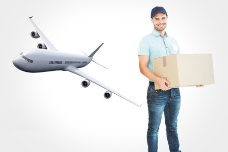 legs crossed at knee: Courier man carrying cardboard box against graphic airplane