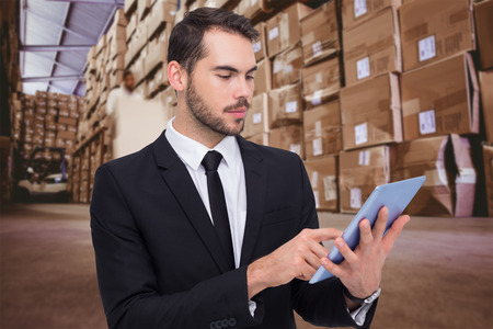 stacker: Cheerful businessman touching digital tablet against worker with fork pallet truck stacker in warehouse