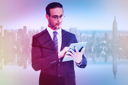 unsmiling: Unsmiling businessman using tablet pc against skyscraper