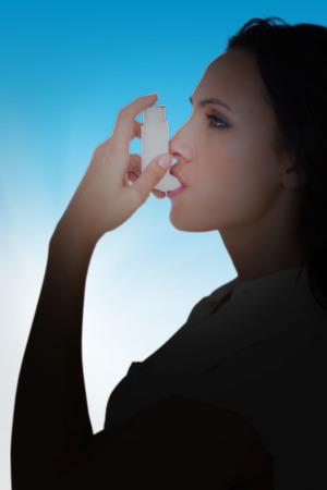 Asthmatic brunette using her inhaler  against blue sky