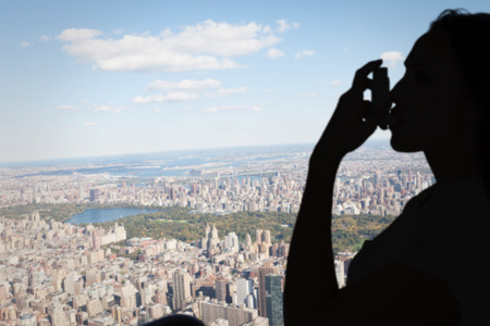 asthmatic: Asthmatic brunette using her inhaler  against new york