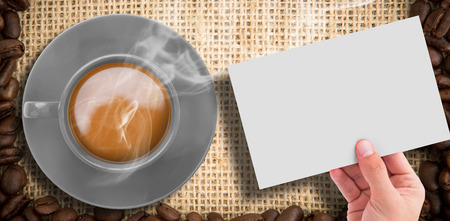indent: Hand showing card against frame of coffee beans