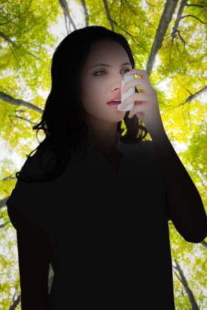 asthmatic: Asthmatic brunette using her inhaler  against low angle view of tall trees
