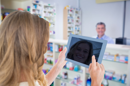 grey hair: Woman using tablet pc  against pharmacist with grey hair standing behind shelves of drugs 스톡 사진
