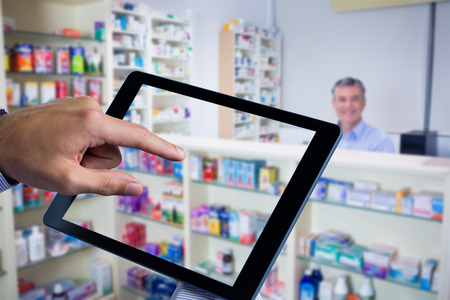 grey hair: Man using tablet pc  against pharmacist with grey hair standing behind shelves of drugs 스톡 사진