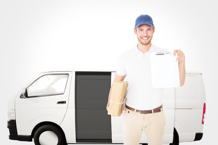 couriers: Happy delivery man holding cardboard box and clipboard against white delivery van
