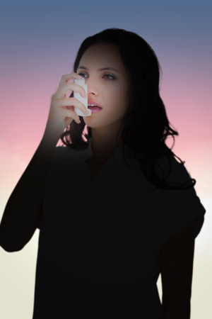 asthmatic: Asthmatic brunette using her inhaler  against magical sky