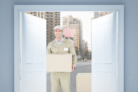 delivery box: Happy delivery man carrying cardboard box against new york street
