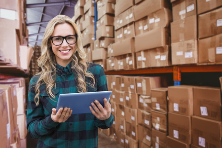 stocks: Pretty blonde with tablet against forklift in large warehouse