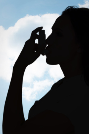 asthmatic: Asthmatic brunette using her inhaler  against blue sky over green field Stock Photo
