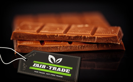 fair trade: fair trade stamp against blurred bar of chocolate Stock Photo