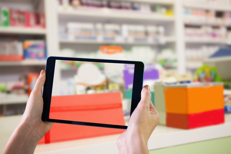 heal sickness: Finger pointing to tablet against close up of shelves of drugs